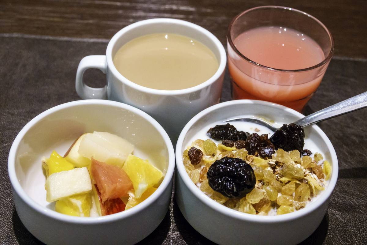 Cereal is served with a bowl of fruit, coffee, and juice.