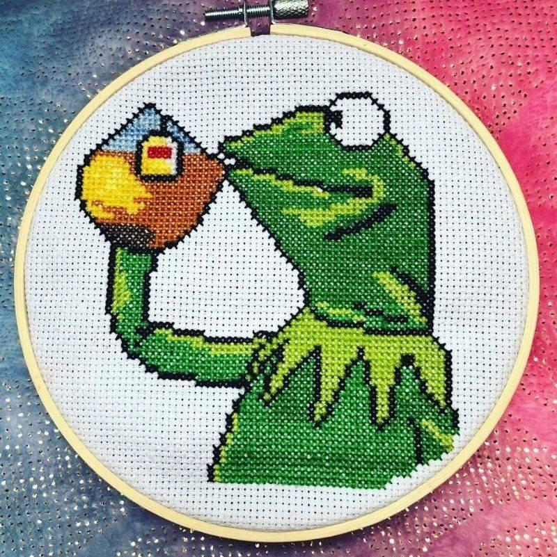 a cross stitch of kermit the frog drinking the tea