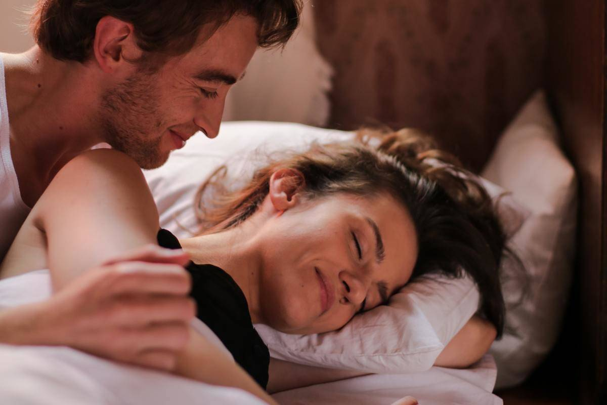 man looking at woman in bed