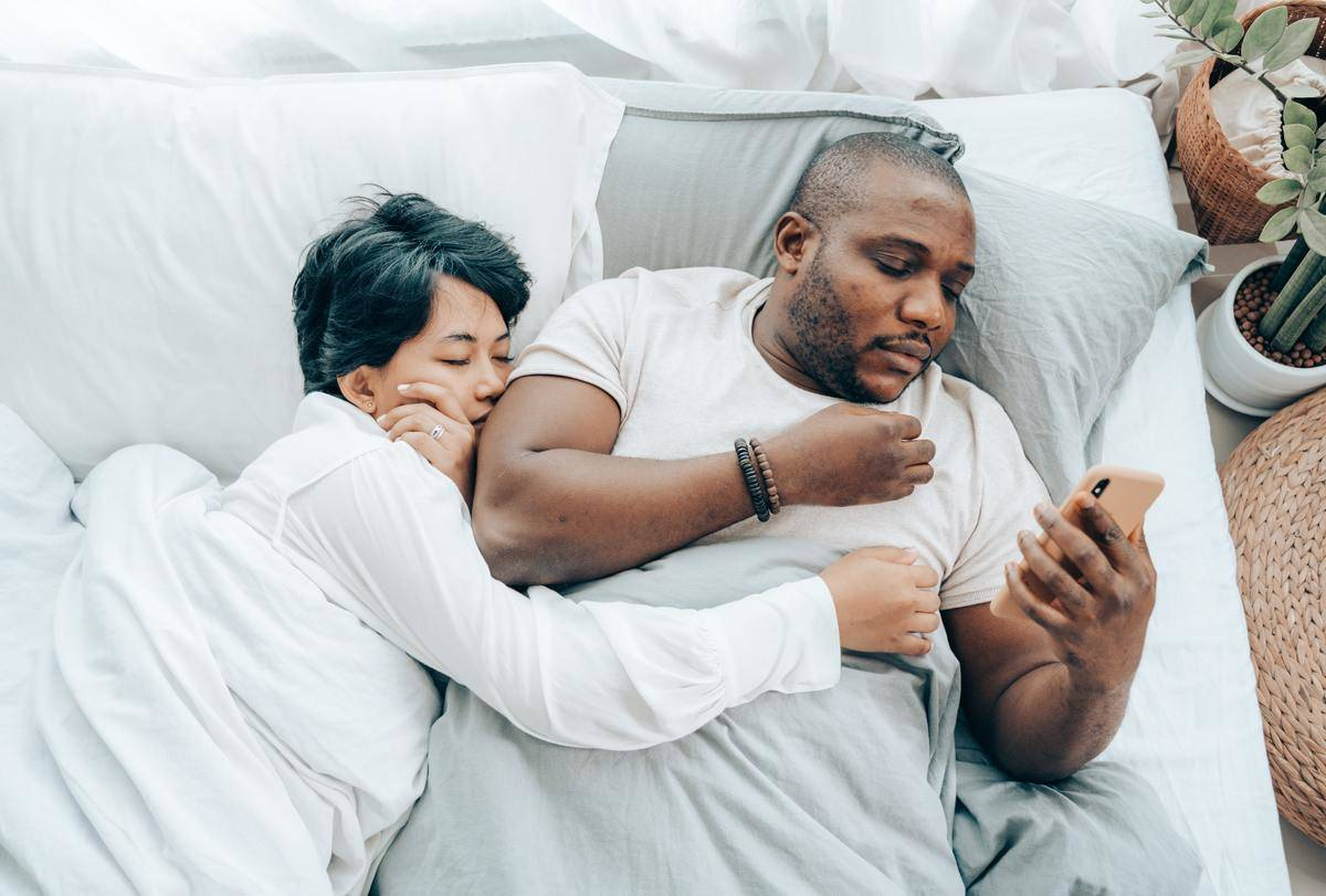 couple in bed man on phone