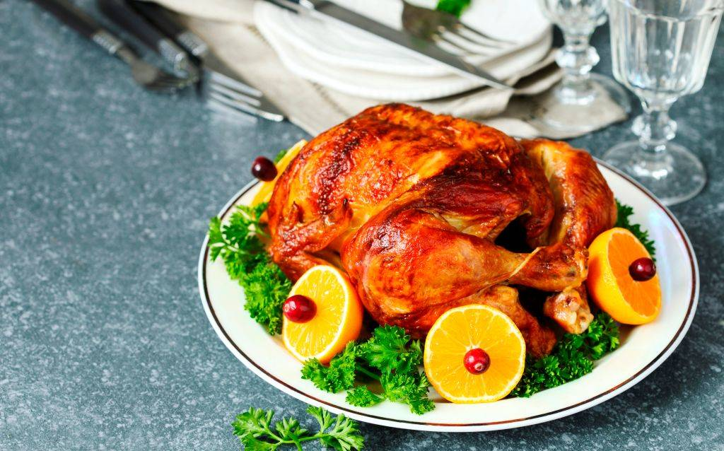 Roasted chicken served with citrus and cranberry on plate