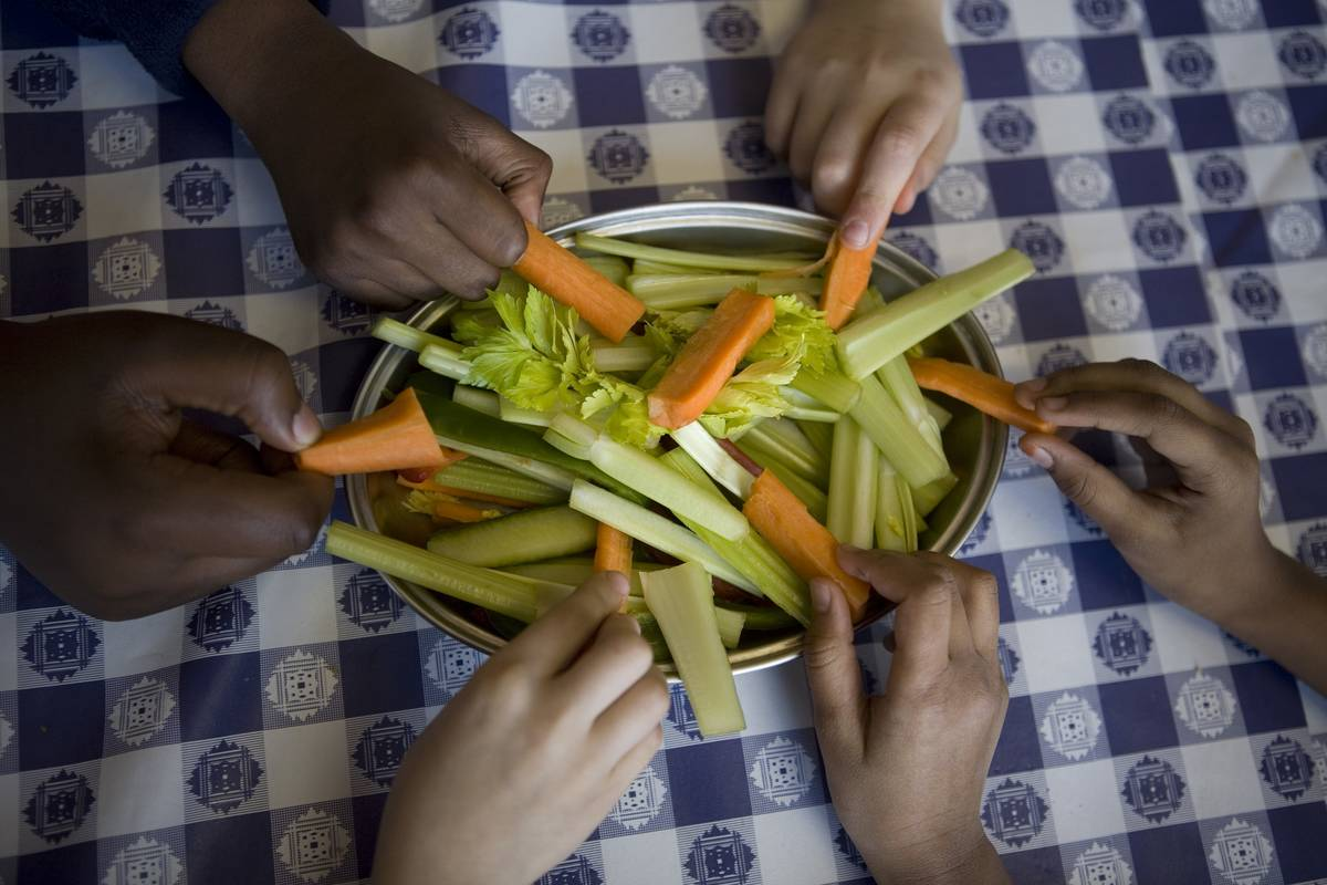 Students pull carrot and celery slices from a plate.
