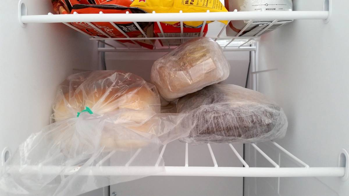 Bread loaves are stacked on a refrigerator shelf.