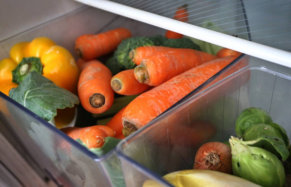 Carrots and other vegetables are stacked in the refrigerator's crispers.