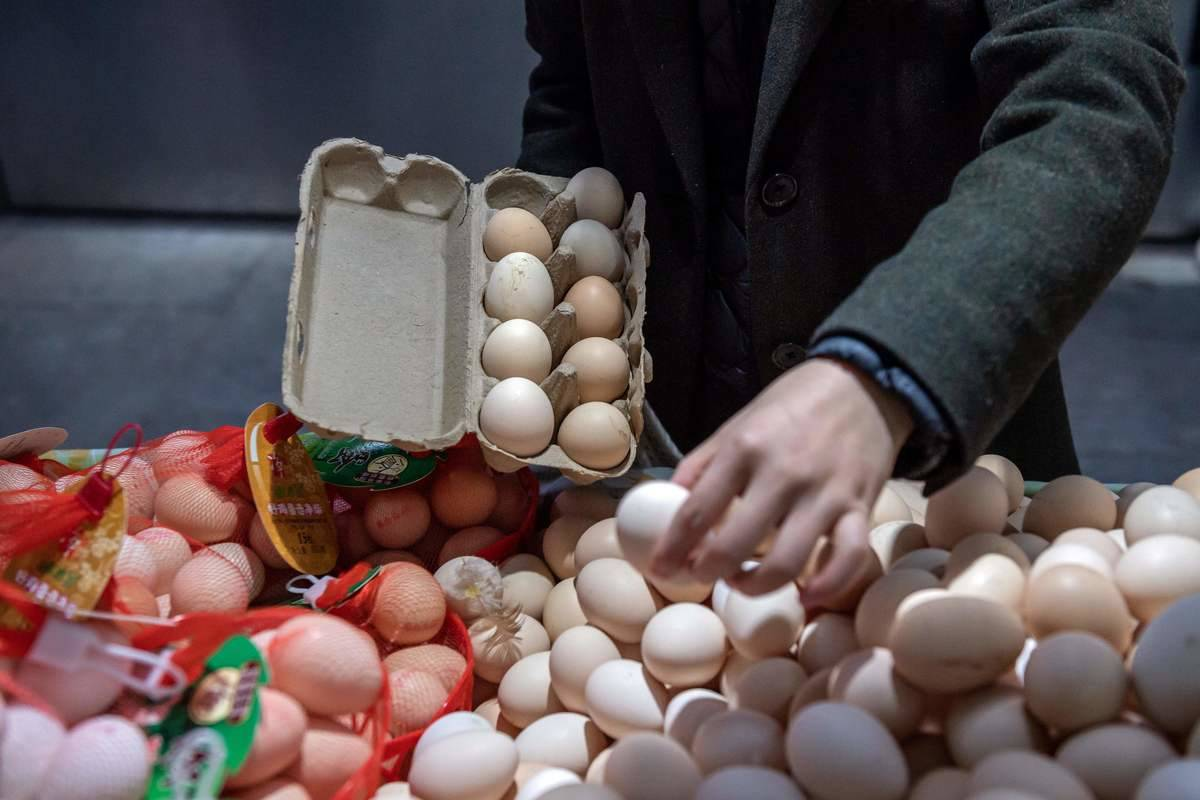 A customer chooses eggs to place in a carton.