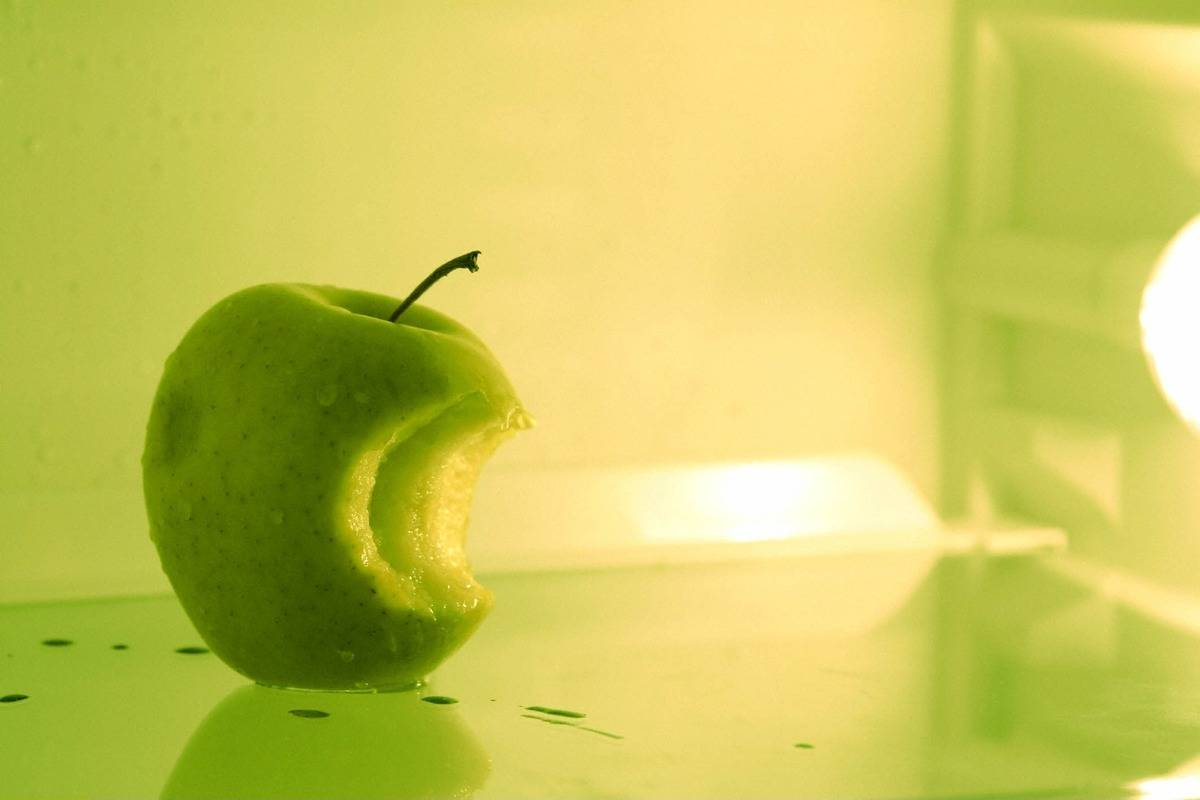 A green apple with a bite in it sits in the fridge.