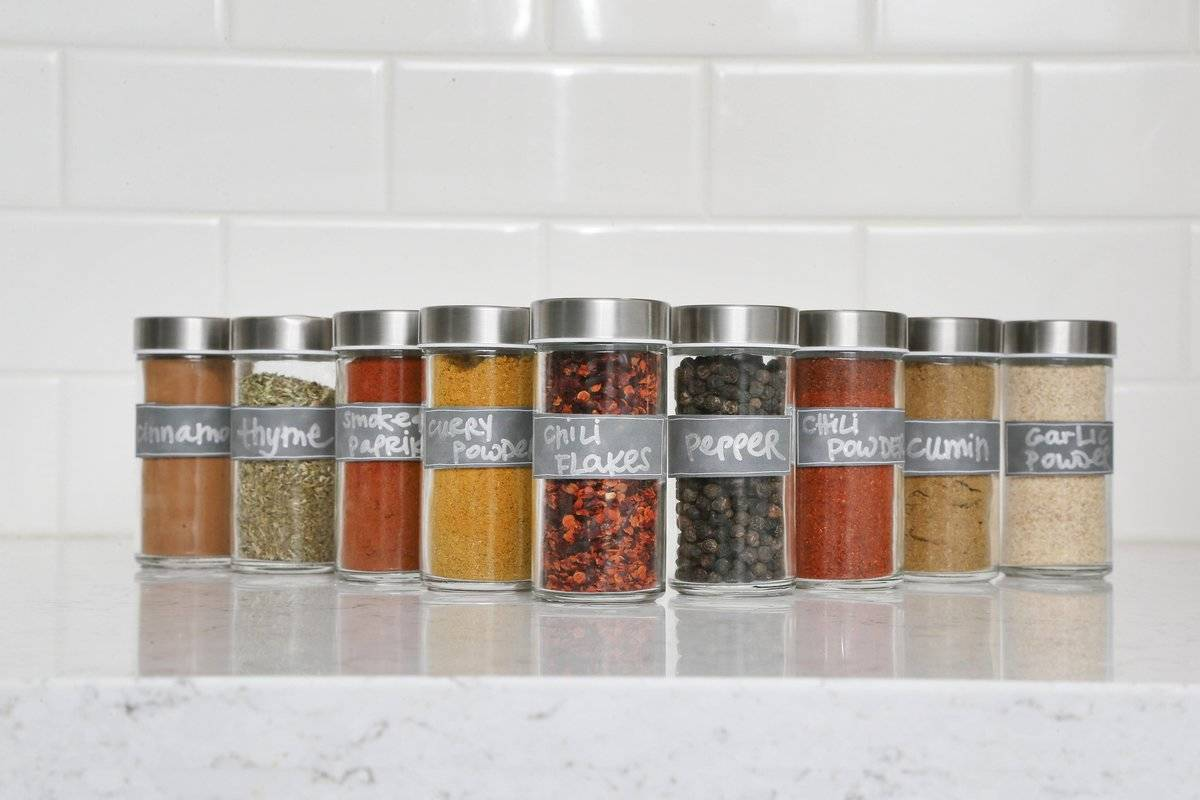 Jars of dried spices stand on a marble counter.