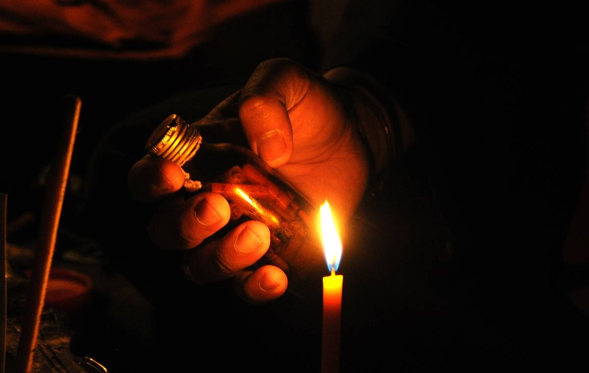 Someone holds a bottle near a candle flame.