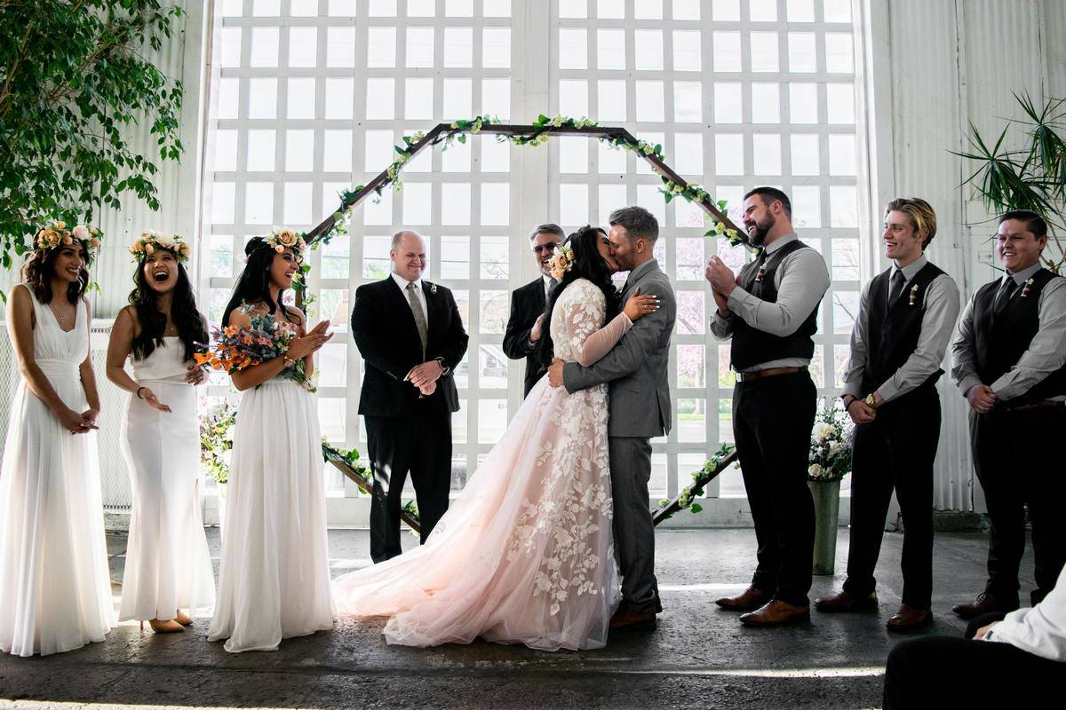 bride and groom on wedding day with bridal party and groomsmen at altar