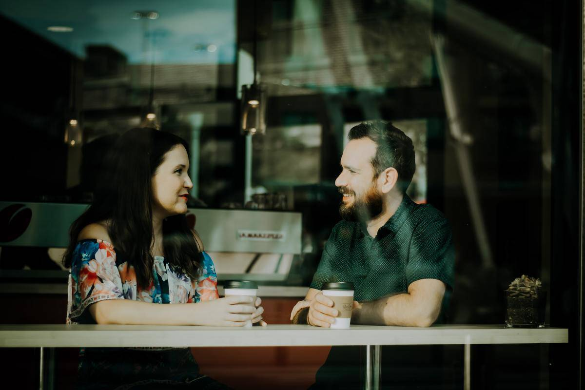 couple having coffee photo through the window