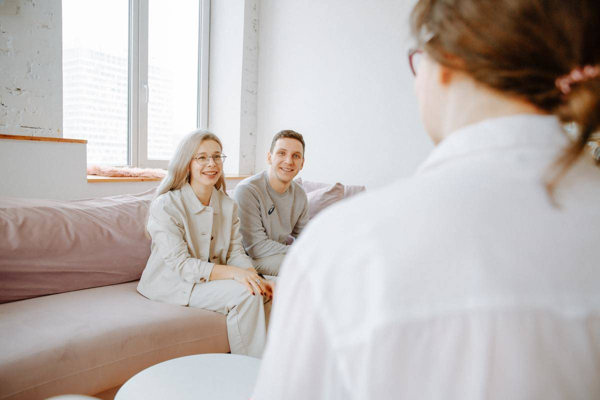 couple smiling looking at therapist seated across from them in bright office
