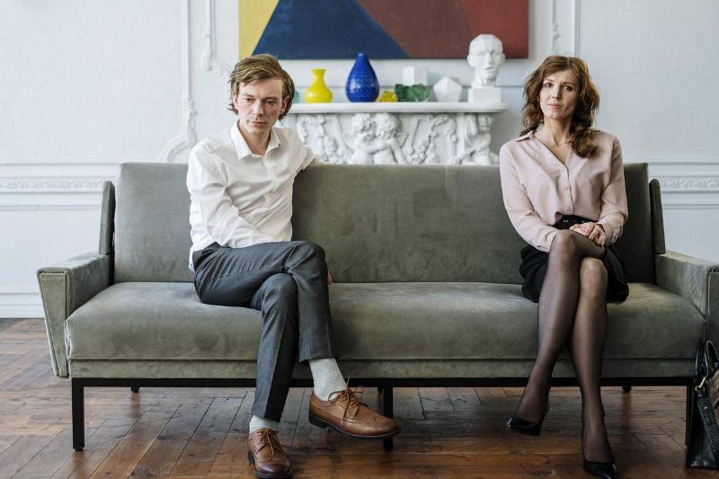 married couple on couch at therapy large space in between them