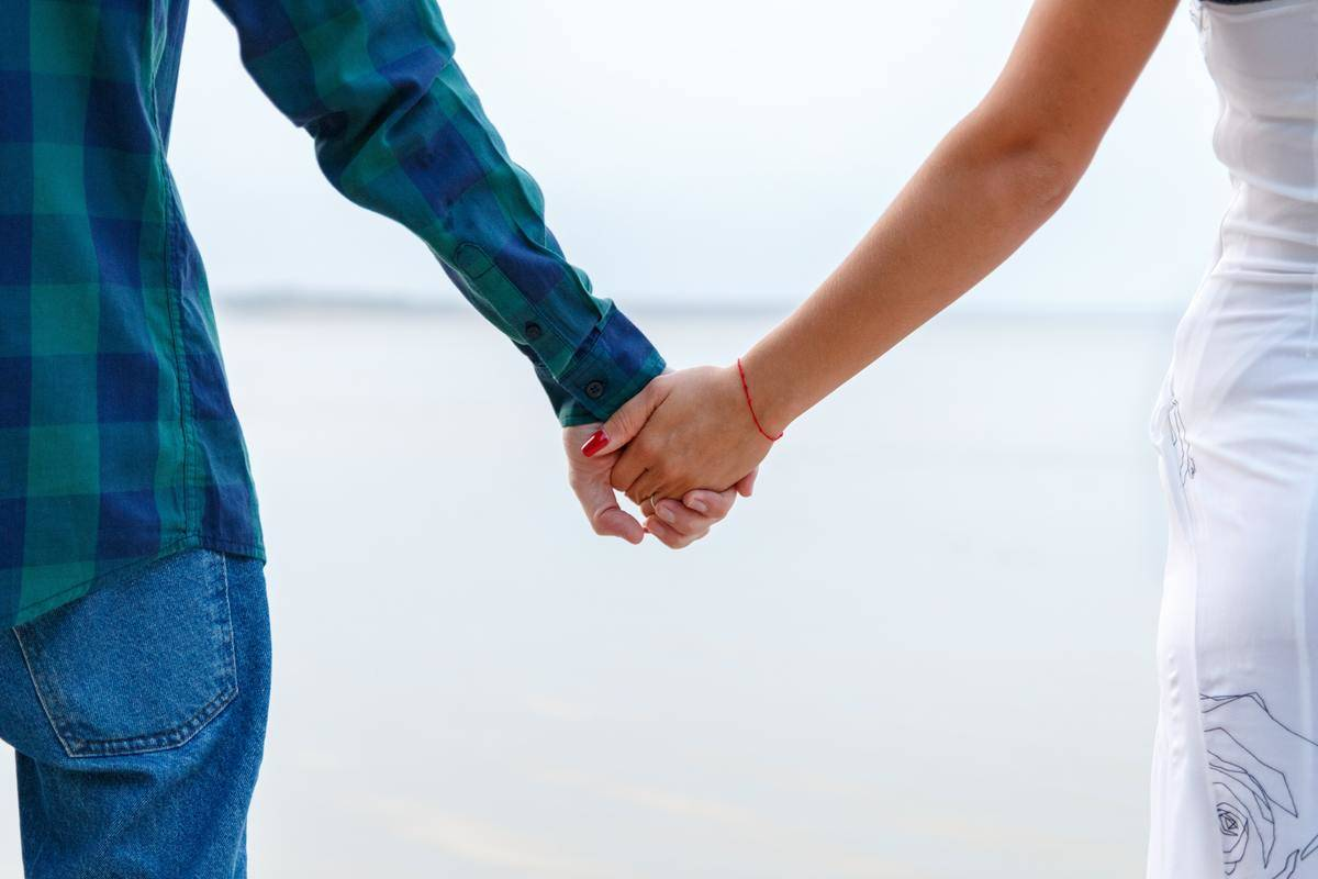 couple holding hands outdoors standing at beach