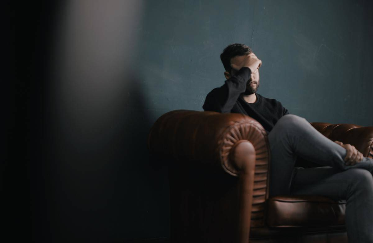 man on brown leather couch alone hand covering eyes
