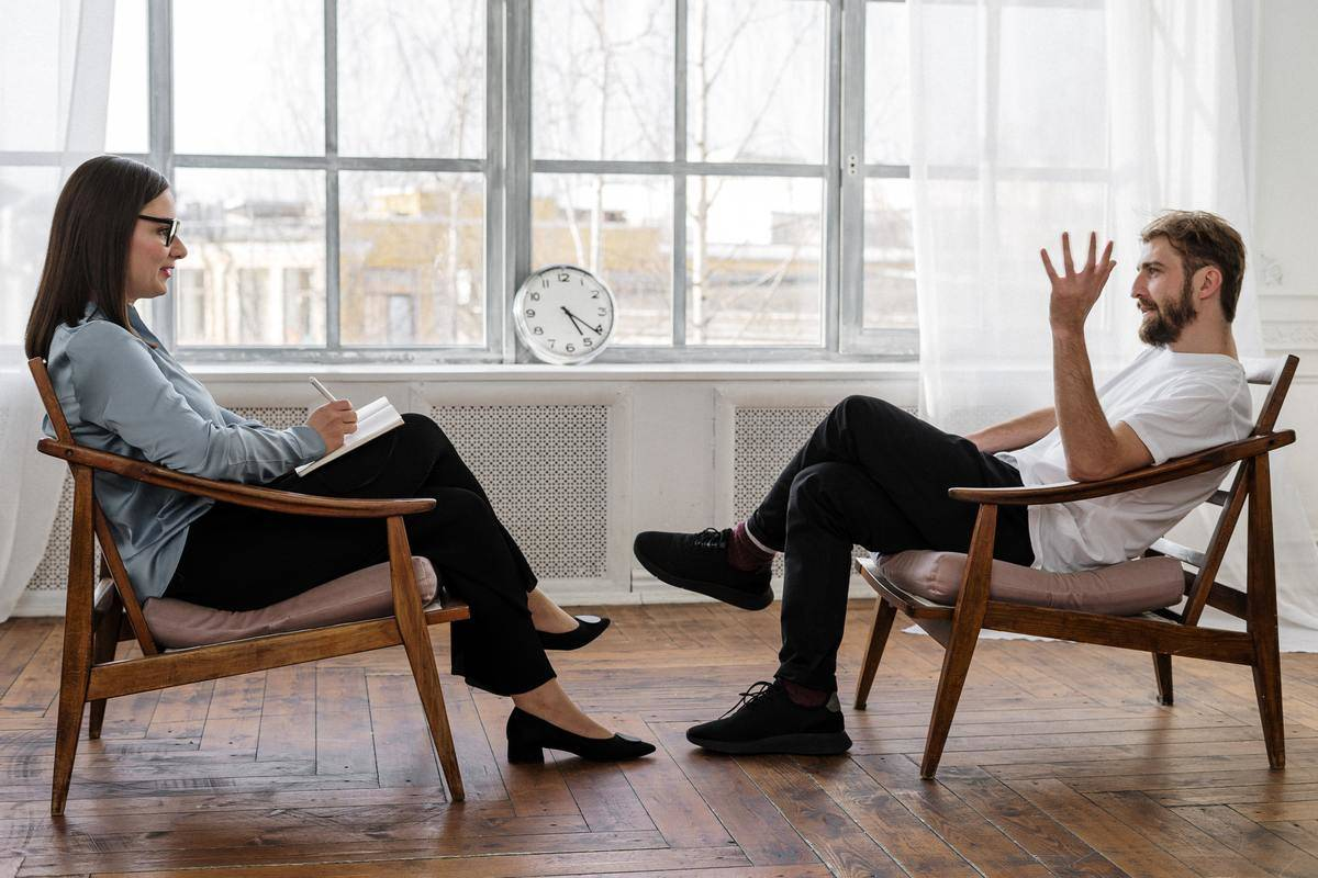 man gesturing with hands speaking to therapist