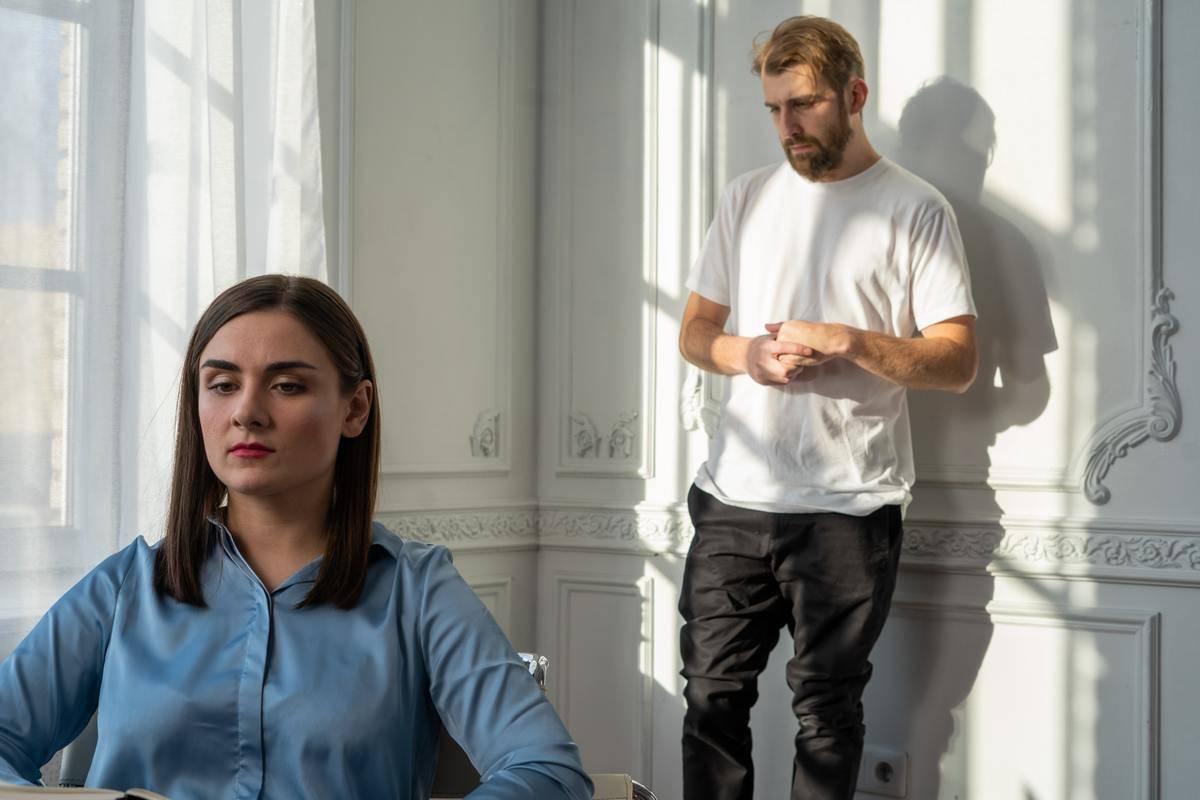 man looking upset standing behind woman seated looking serious