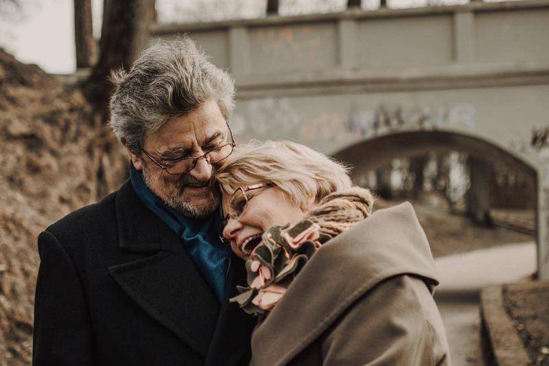 older woman laughing leaning on older man hugging her