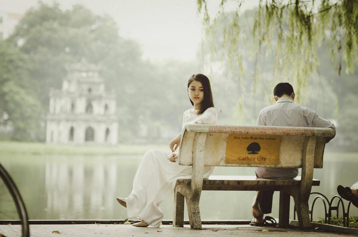woman on bench facing away from man looking down