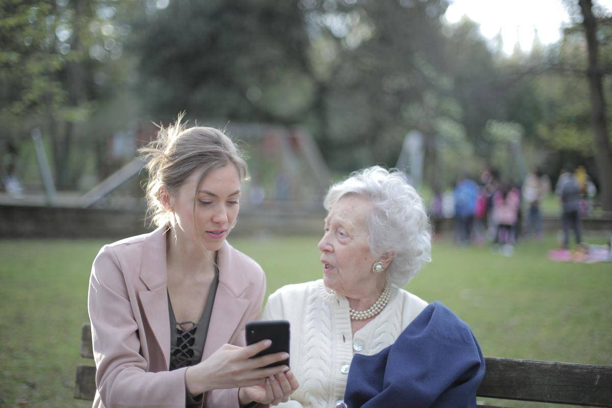 woman holding phone seated on bench with grandmother talking