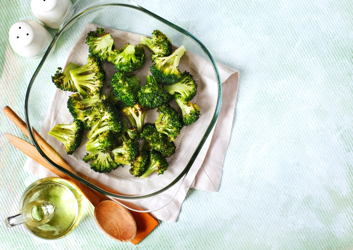 Baked broccoli sits in an oven-safe glass bowl.