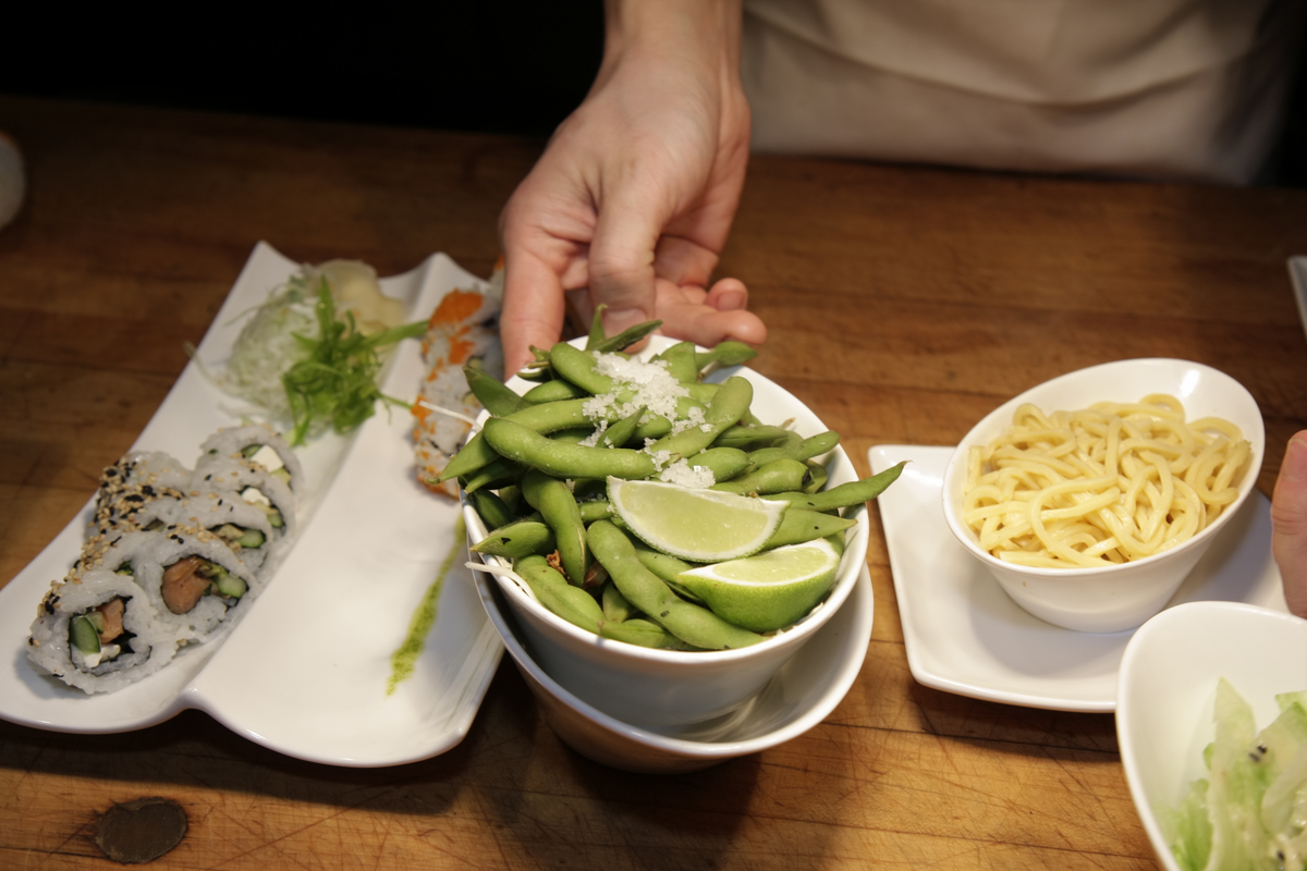 A person holds a bowl of soy over a meal of sushi and low mein.