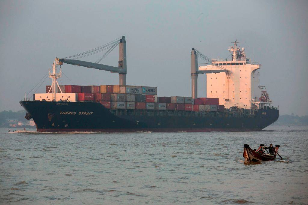 A man rides in a small boat past a container ship in the Yangon River