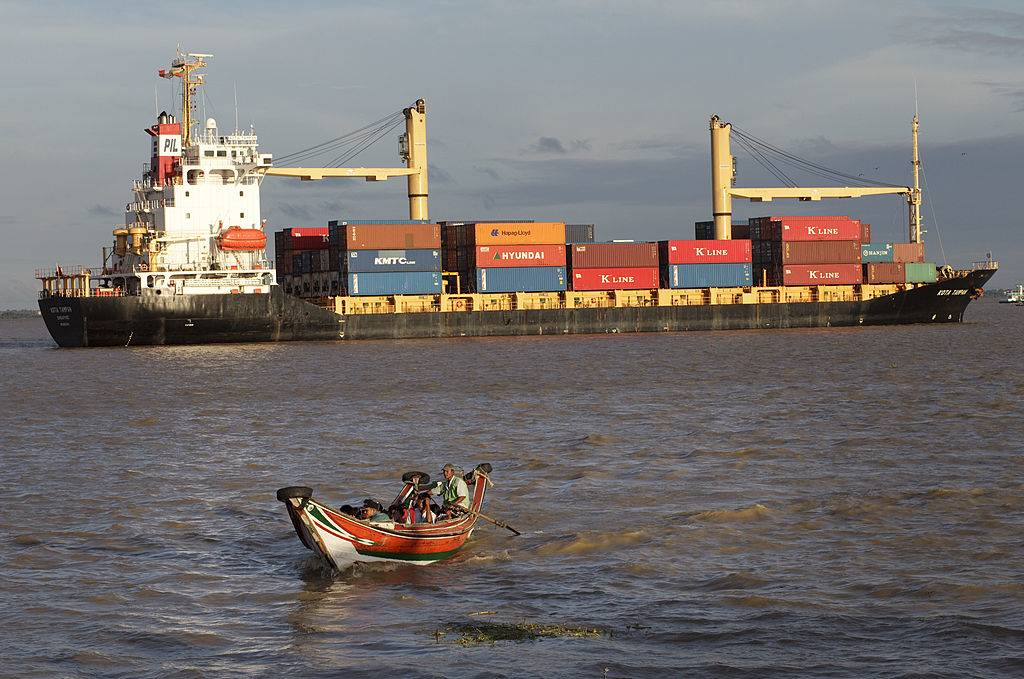 A small commuter boat makes way in front of container ship