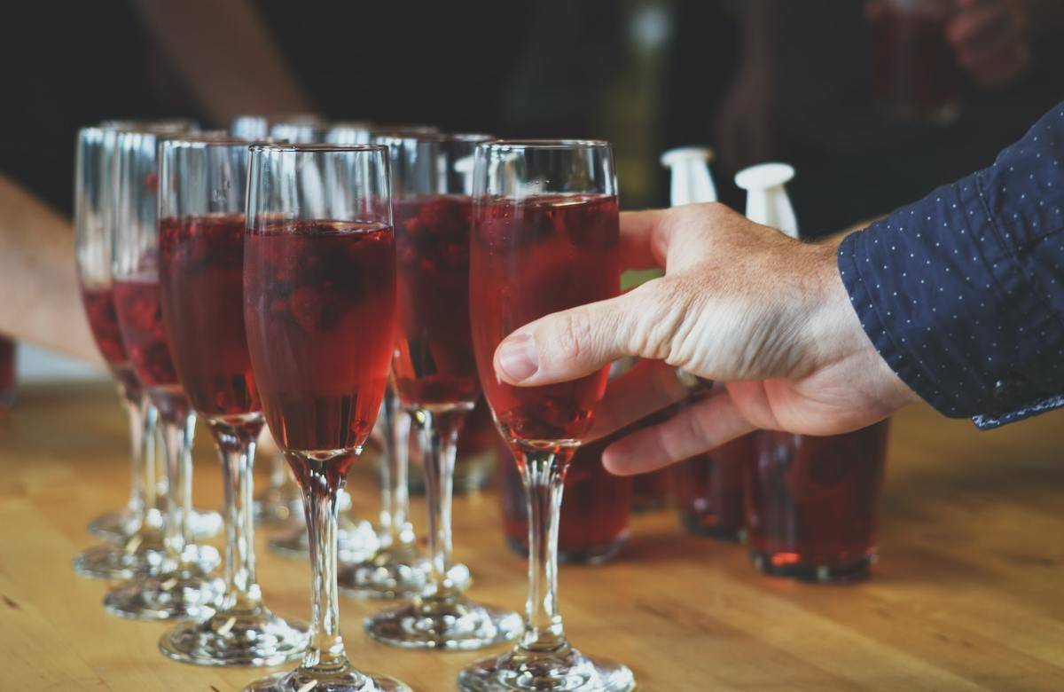 A person picks up a glass of cranberry juice from a serving tray.