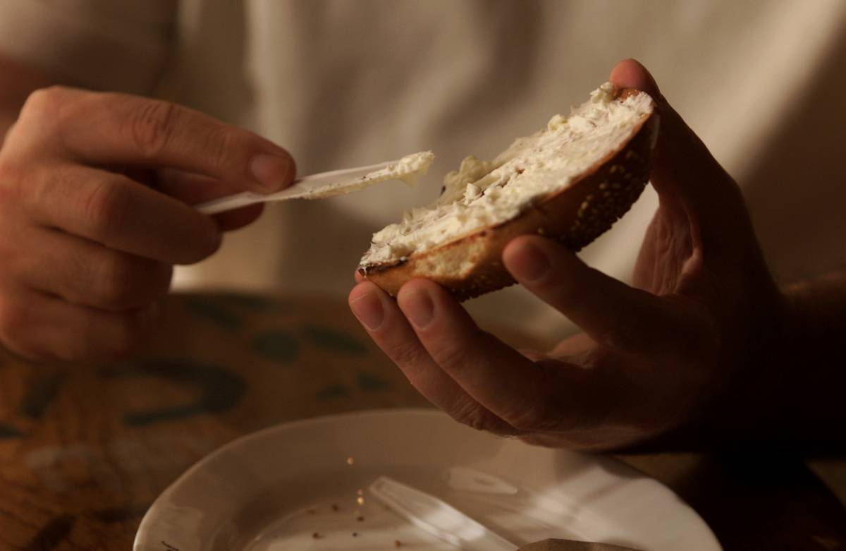 A person spreads cream cheese on a bagel.