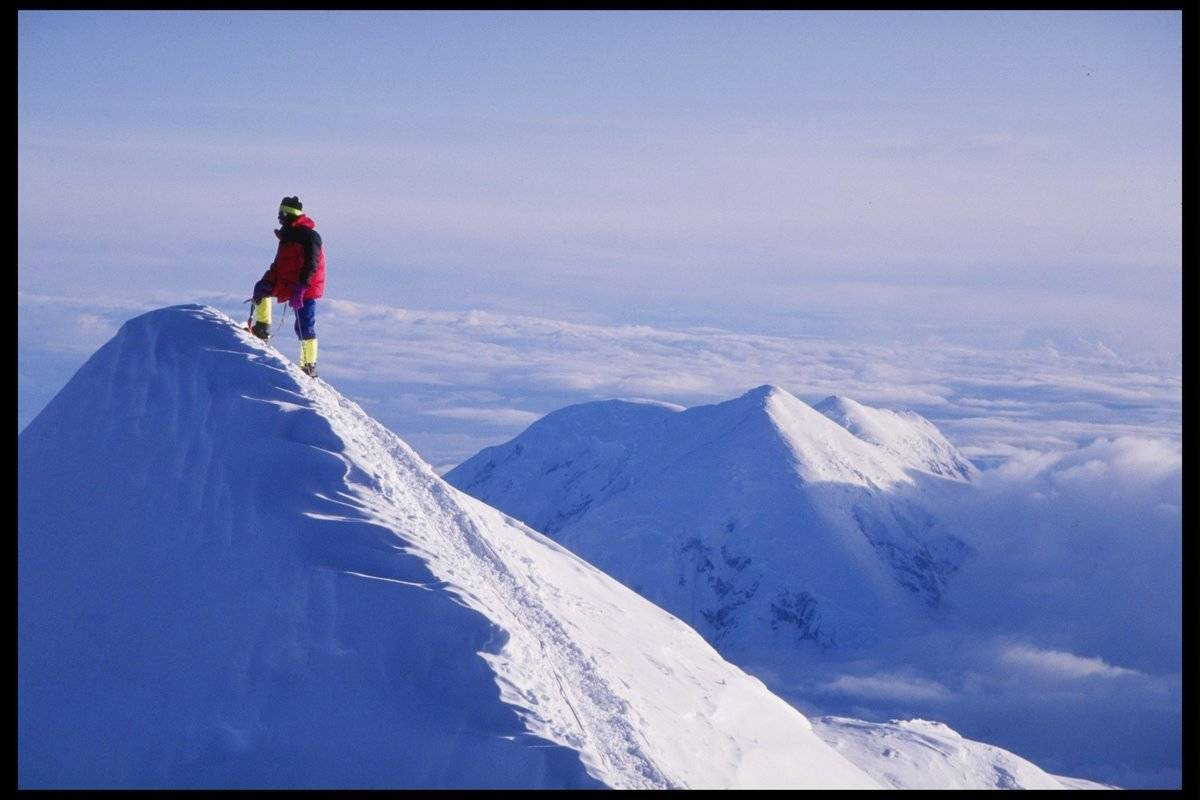 A lone climber stands on the Summit Ridge at Denali on Mount McKinley, Alaska.