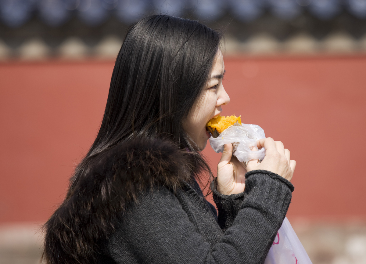 Girl eats a sweet potato at the Ming Dynasty Temple of Heaven, Beijing, China.