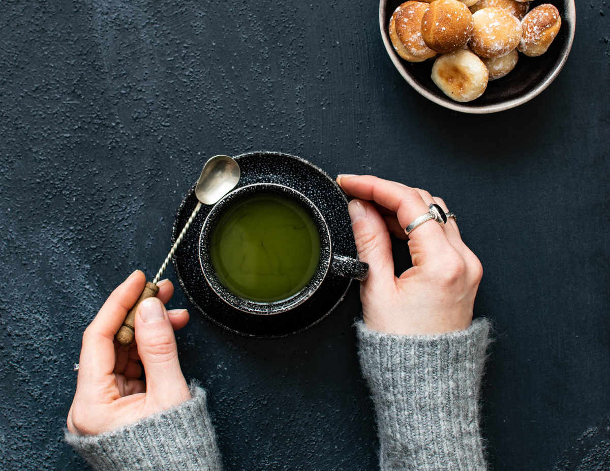 A woman lifts a spoon out of a cup of green tea.
