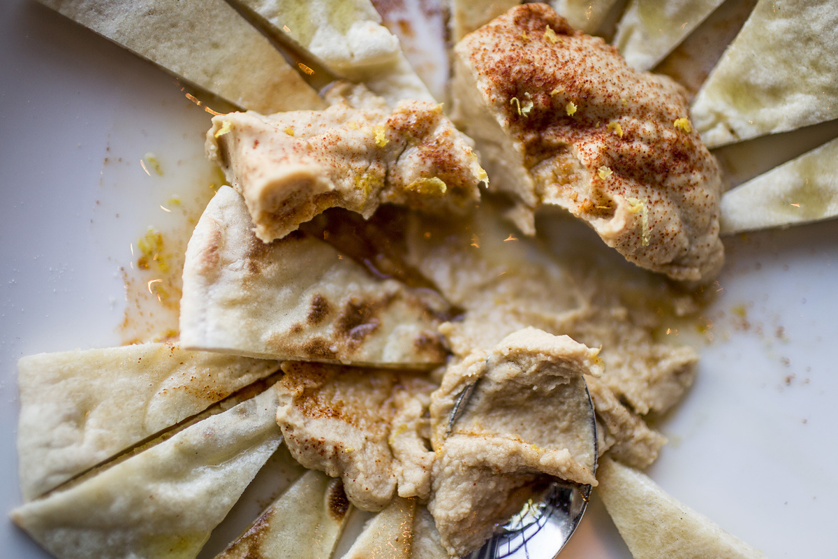 Pita and bread are dipped into a pile of hummus.