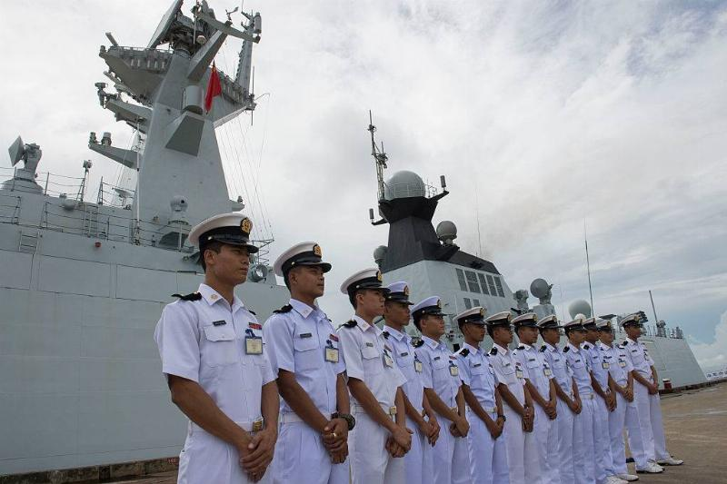 Myanmar navy personnel stand near a ship