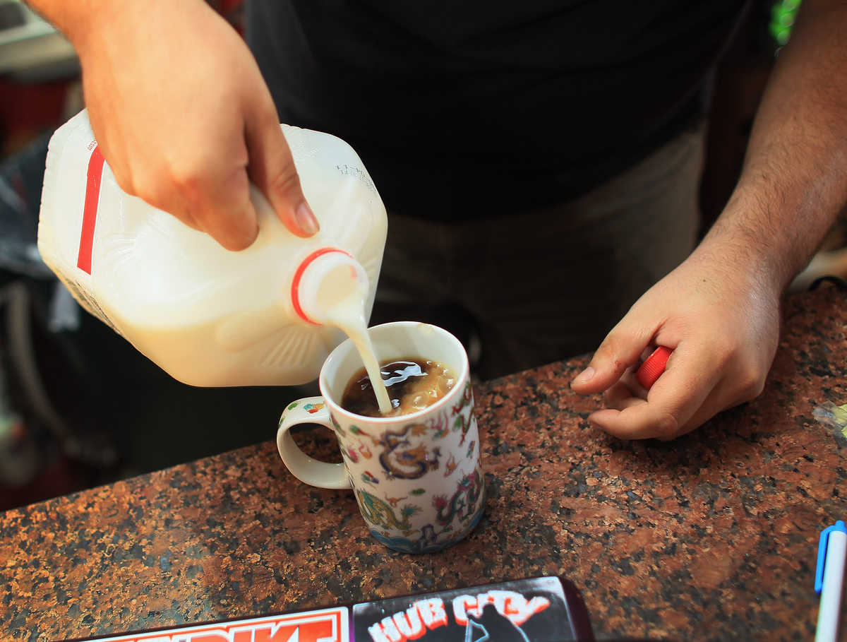 Kyle Kaly adds milk to his cup of coffee at the Undergrounds Coffeehaus.