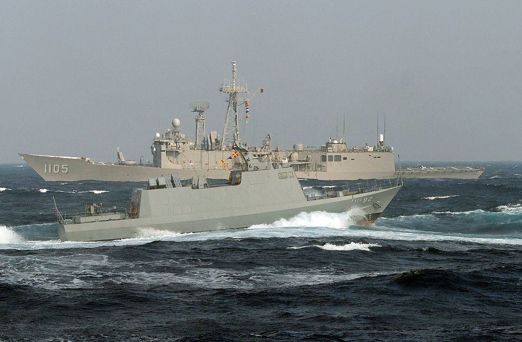 A locally made Kwong Hua six speed boat sails past a US-made frigate
