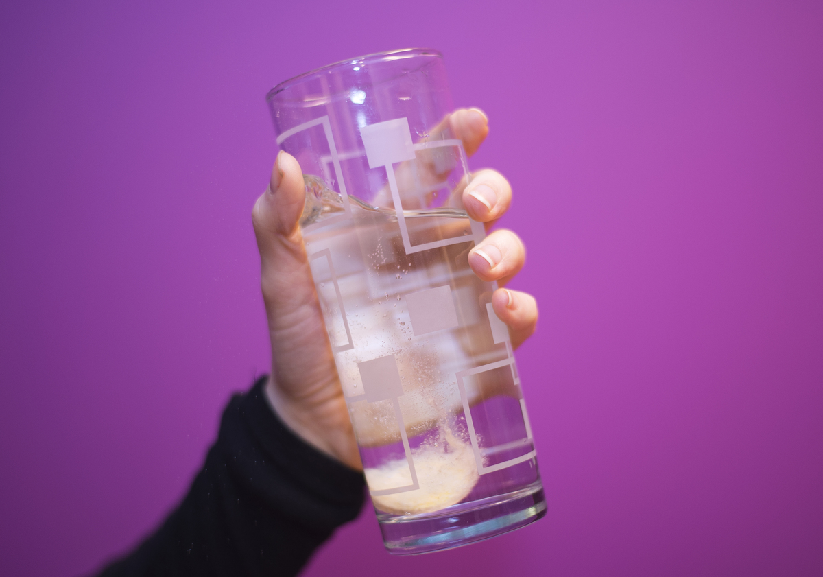 A vitamin C tablet dissolves into sparkling water.