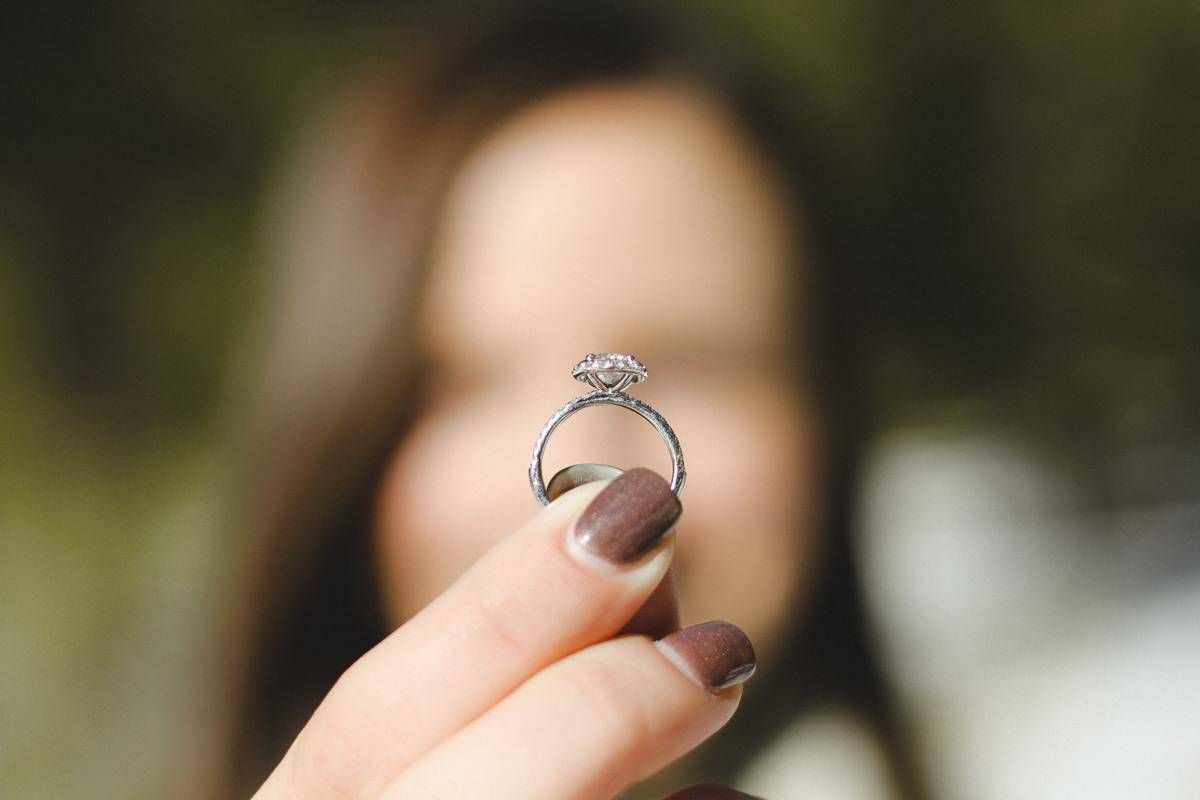 woman holding up diamond ring