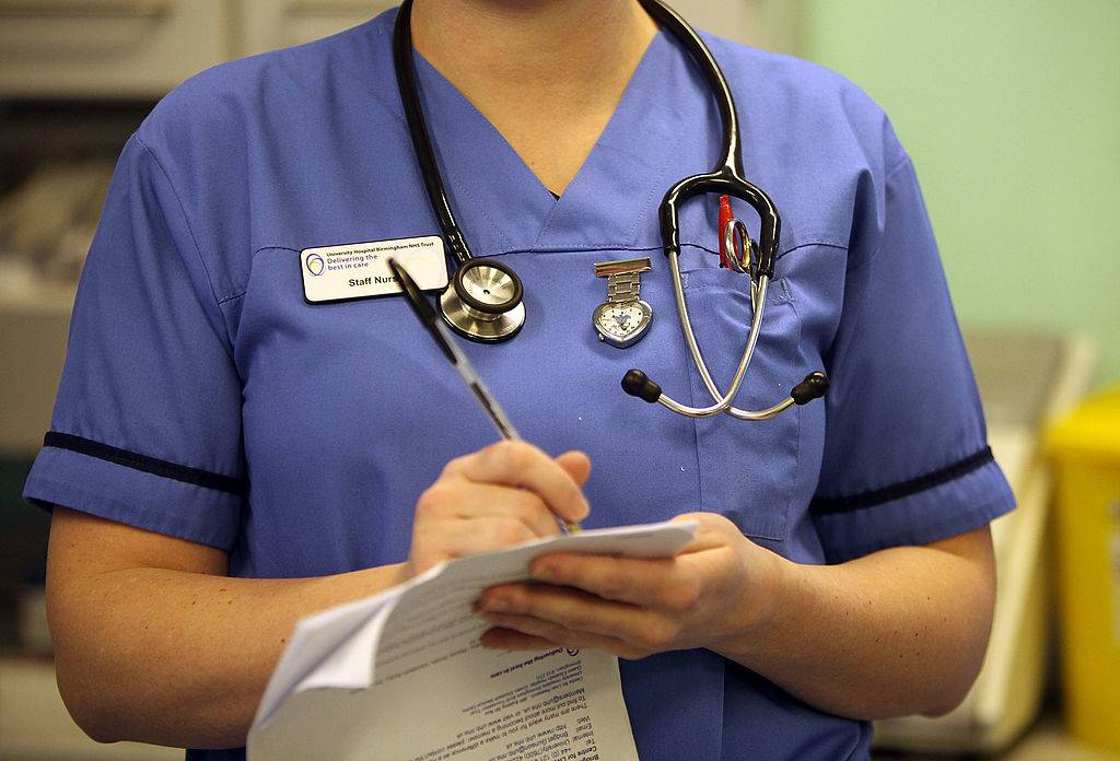 a nurse writes on a piece of paper and wears a stethoscope