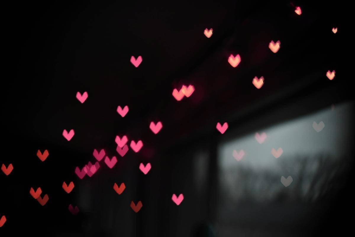a bunch of pink hearts on a black background