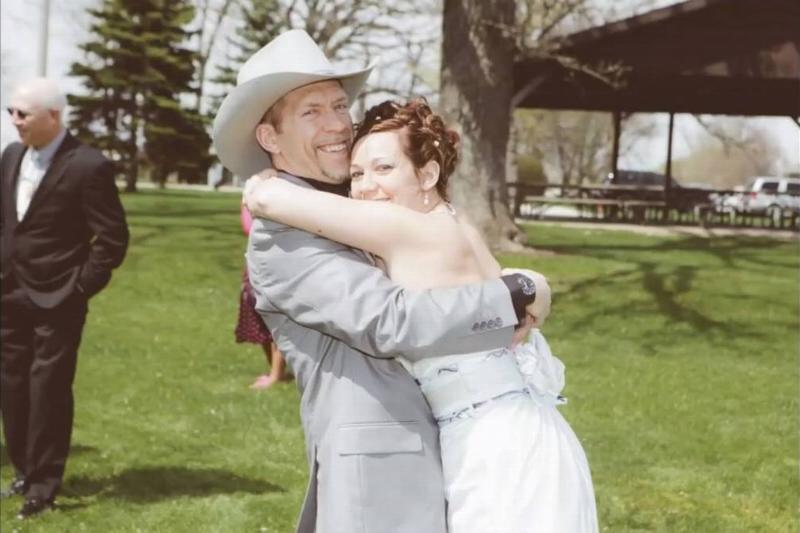 Carrie and Craig Kolinski hug at their wedding.
