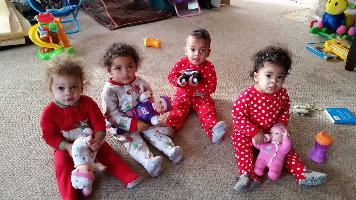 Two sets of the Kolinski twins sit on the floor with toys.