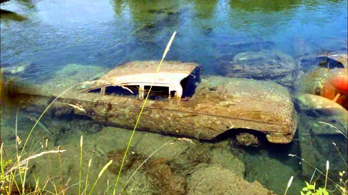 A 1959 chevy impala is submerged in a lake.
