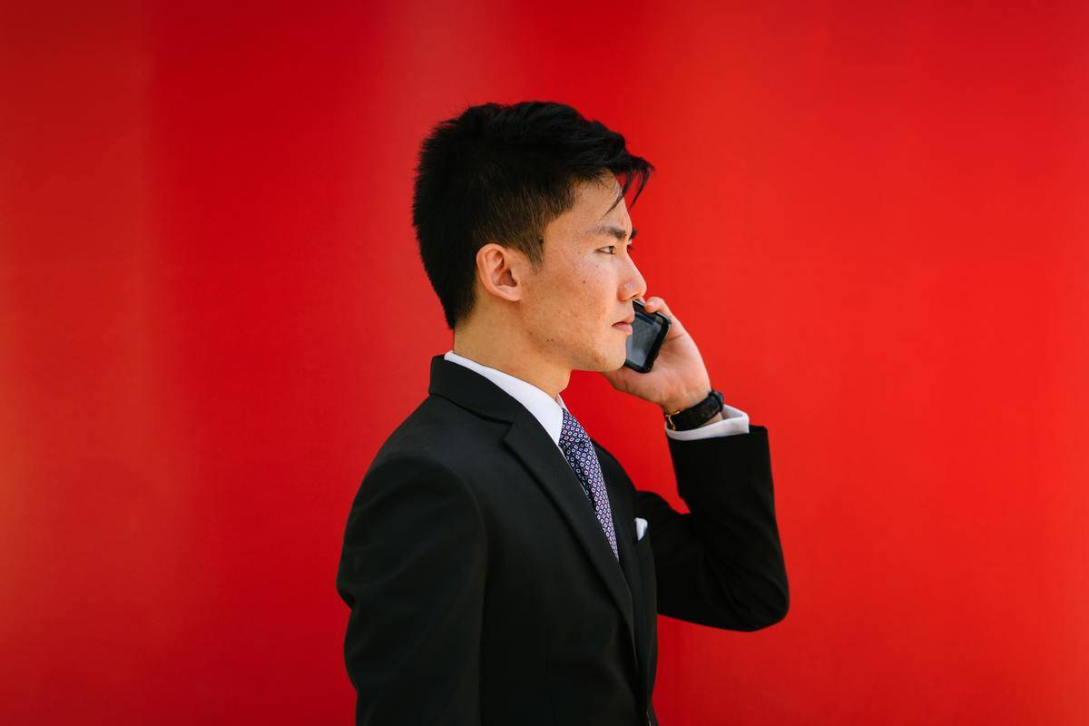 Man in suit standing talking on smartphone, bold red background wall.
