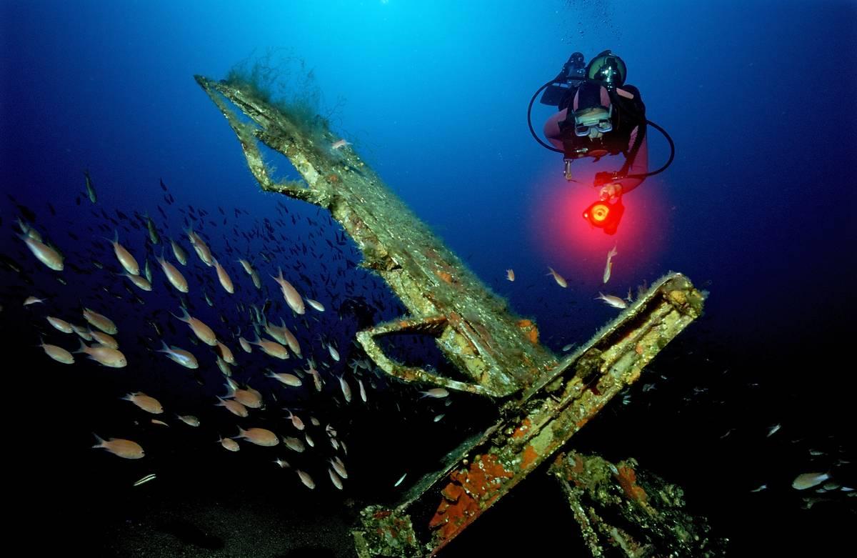 A scuba diver swims by a sunken Messerschmidt 109 plane.