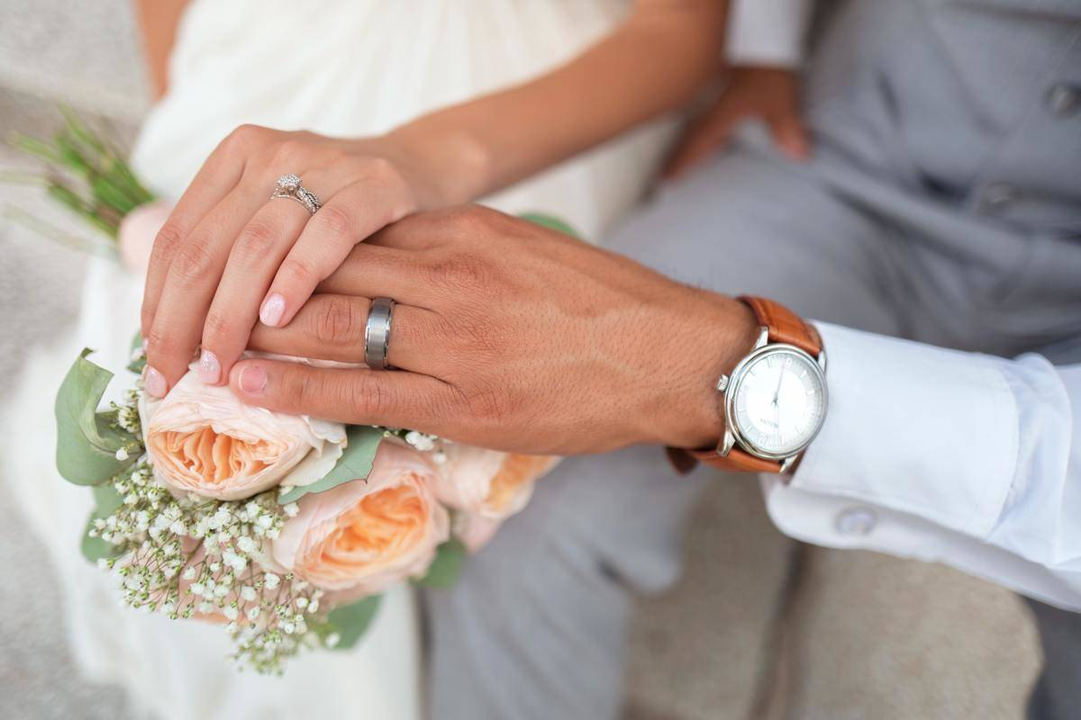 Woman holding man's hand with visible wedding rings, placed on bouquet of peach flowers.