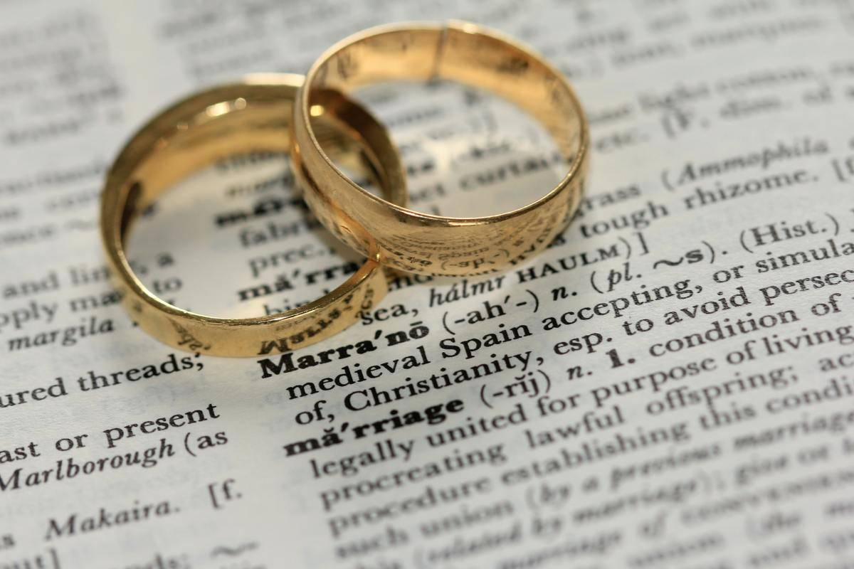 Two gold wedding bands laid on a page in book beside the definition of marriage