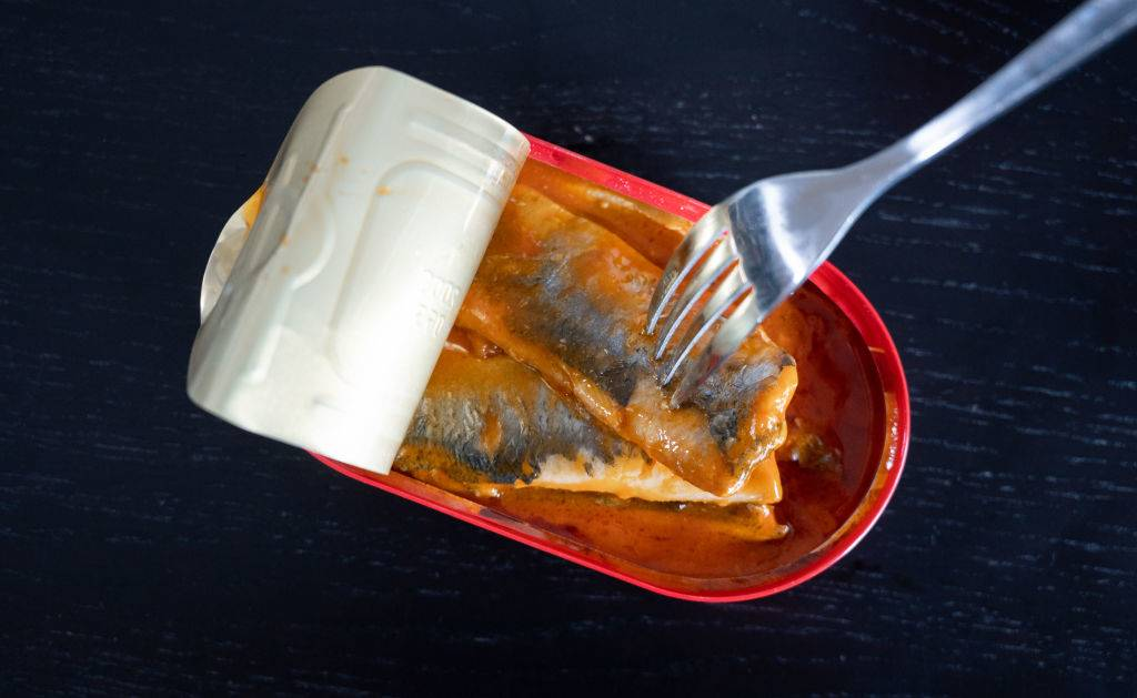A fork is stuck in a tin of herring fillets