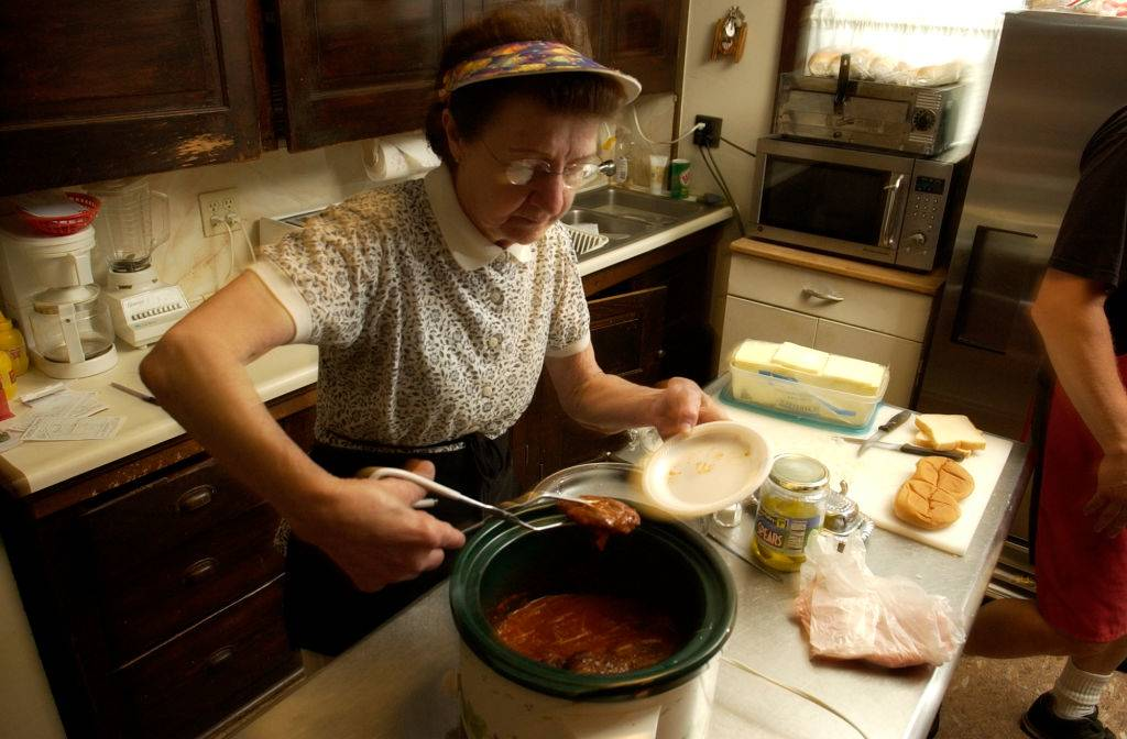 an old woman cooking meat in a crock pot