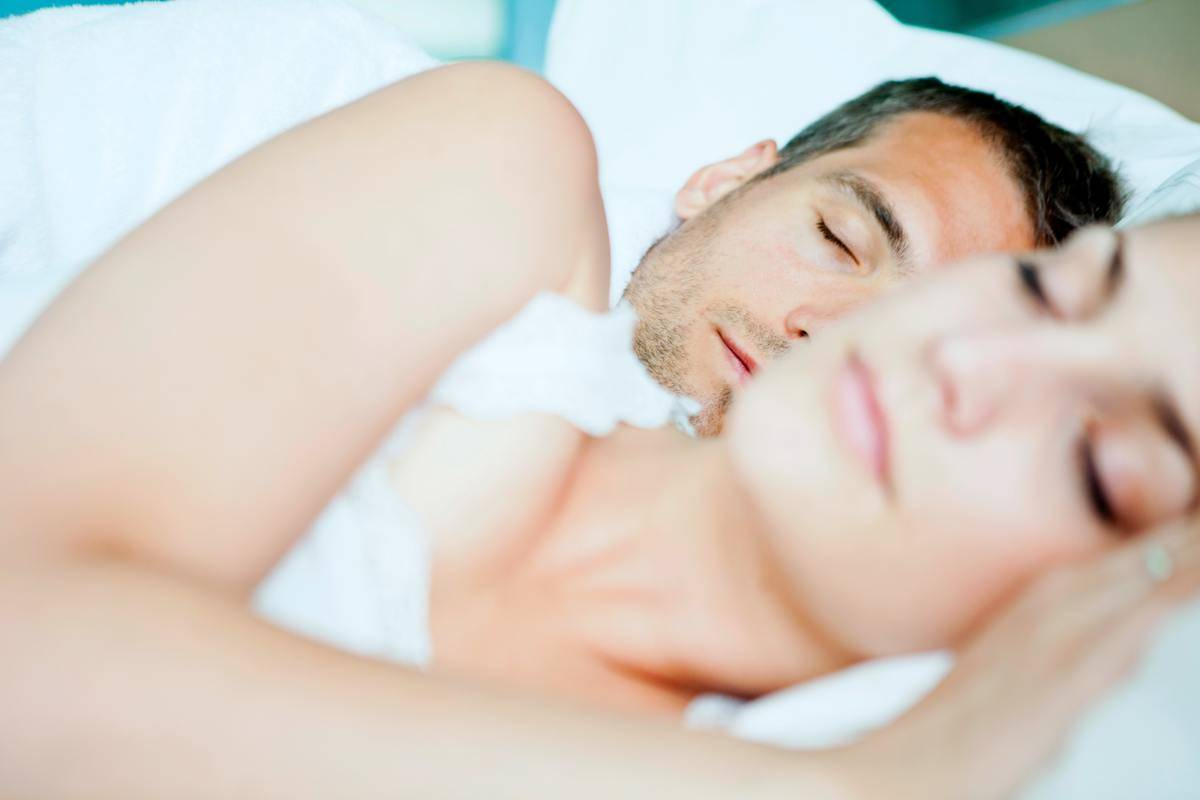 man and woman sleeping in bed with woman out of focus